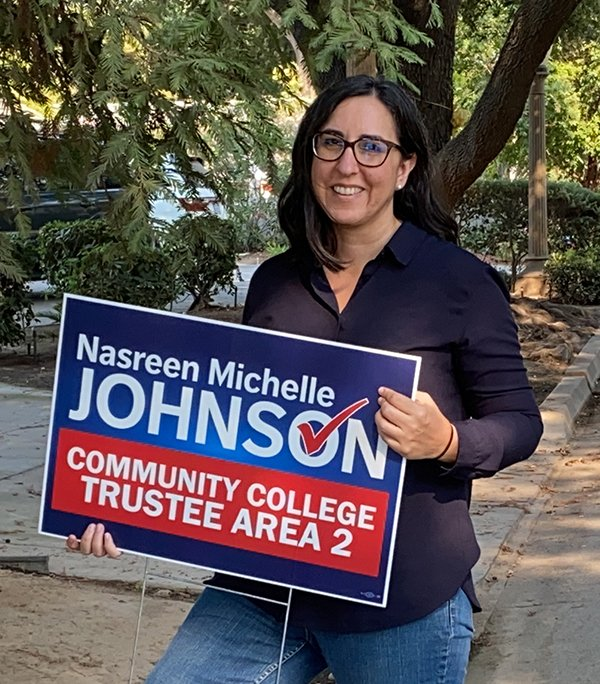 Nasreen Johnson holding up campaign sign in the yard of a supporter.